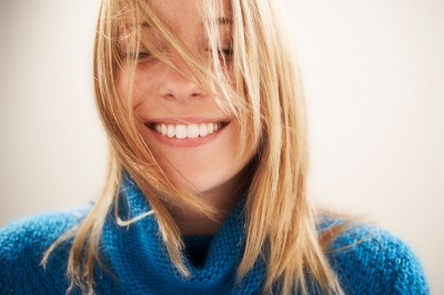 Beautiful smiling blonde woman with hair in face